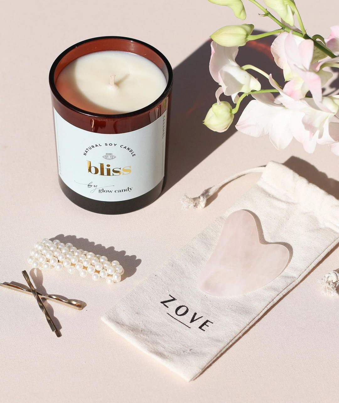 A photograph by one of Glow Candy's customers, shared to social media. The photo shows the 'Bliss' candle positioned alongside a beauty product by Zove and a bouquet of flowers.