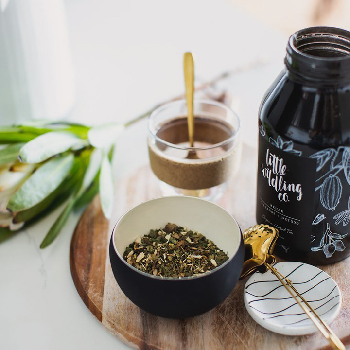 A collection of things sits side by side on a circular wooden chopping board. The collection includes a glass jar of Little Wildling Co loose leaf tea, a gold tea strainer, a small bowl of loose leaf tea and a glass keep cup.