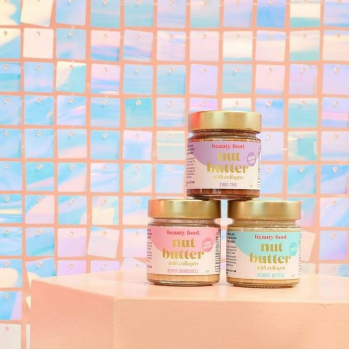 Three jars of Beauty Food Nut Butter sit stacked atop a pink podium, in front of a colourful wall of metallic mosaics.