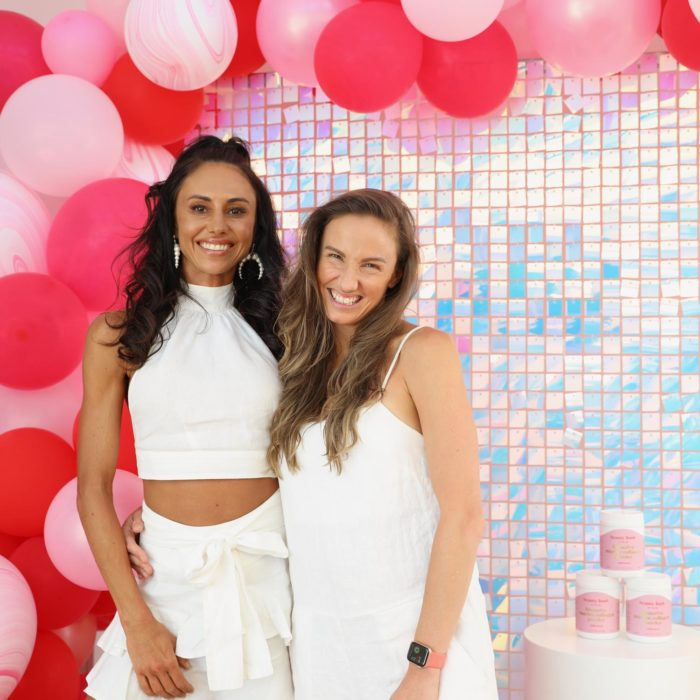 Founders Libby and Veronika smile while standing alongside a podium containing tubs of Beauty Food Collagen Powder. The photo was taken at a Beauty Food event and there is a colourful mosaic wall and pink and red balloons in the background.