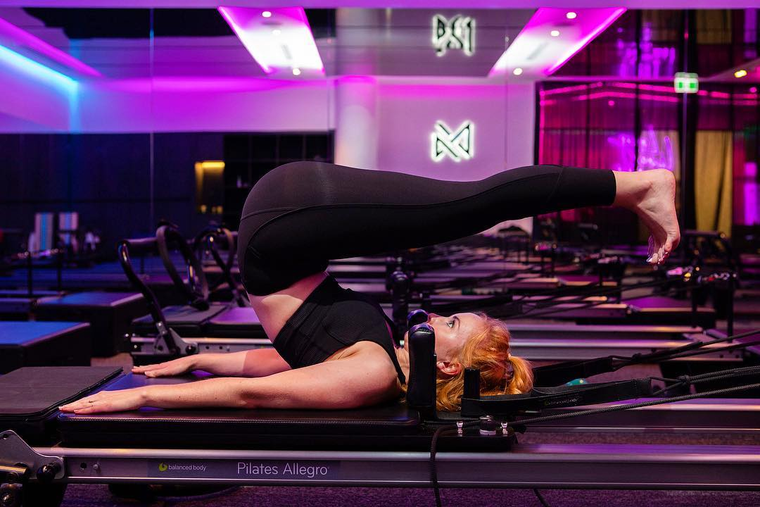 A Vive Active trainer using a reformer in the foreground. The brand's icon lit up in neon in the background.