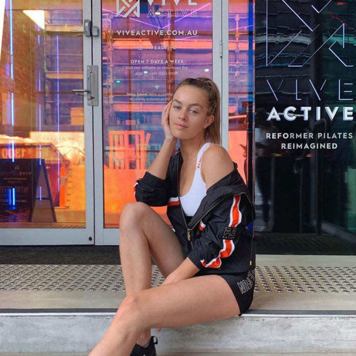 A Vive Active customer sits on the steps outside Vive Active Double Bay. The entrance facade and signage is visible behind her.