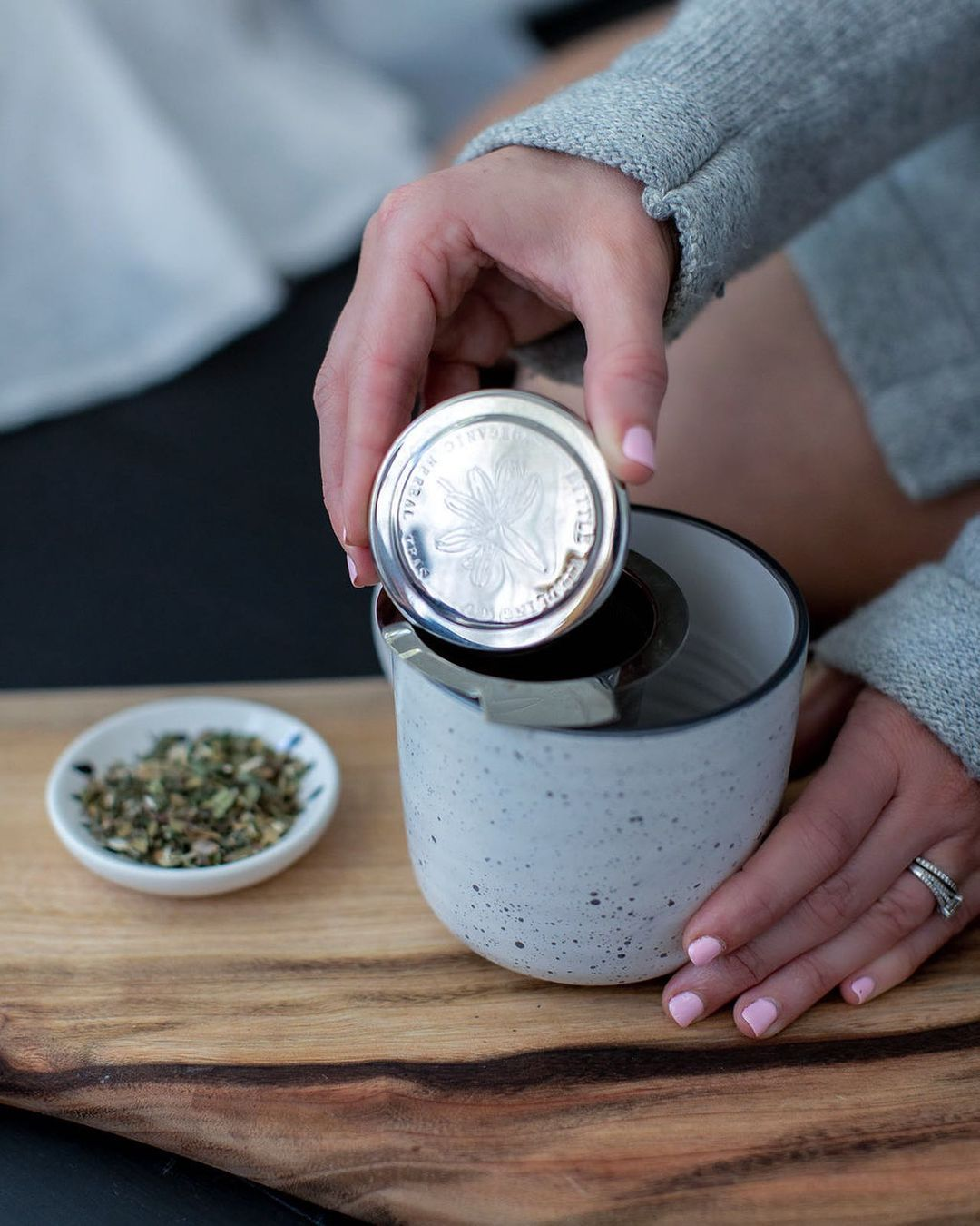 A person with pink nail polish holds a tea strainer at the edge of a ceramic mug. The strainer is branded with a floral illustration and the brand name.