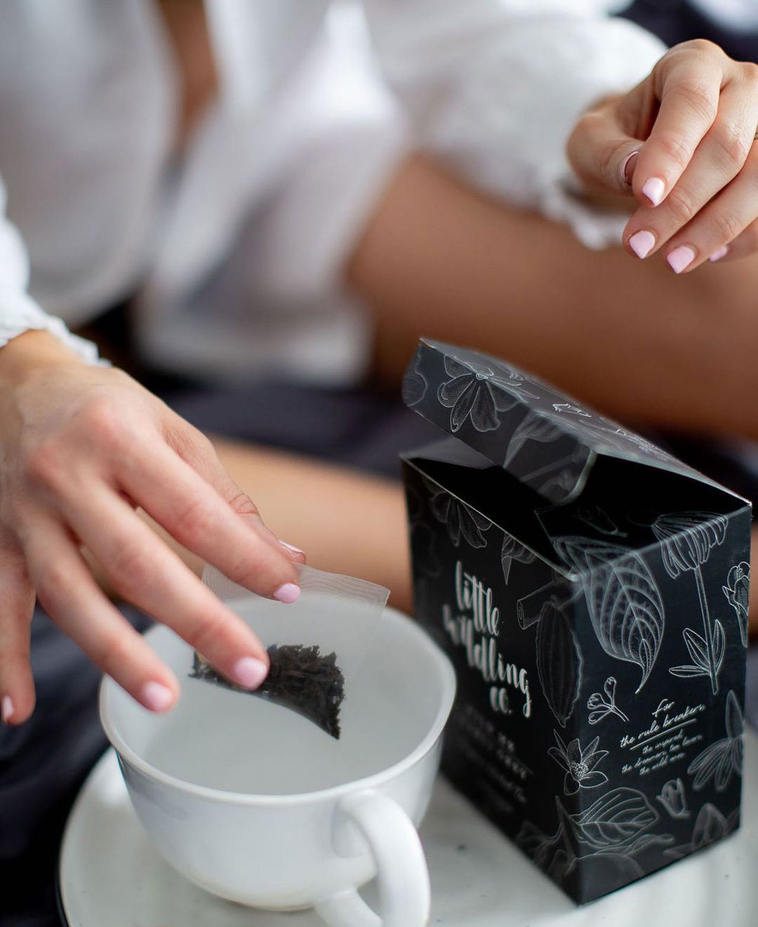 A person holds a teabag above a mug of hot water, about to drop it into the mug. A box of Little Wildling Co tea is visible next to the mug.