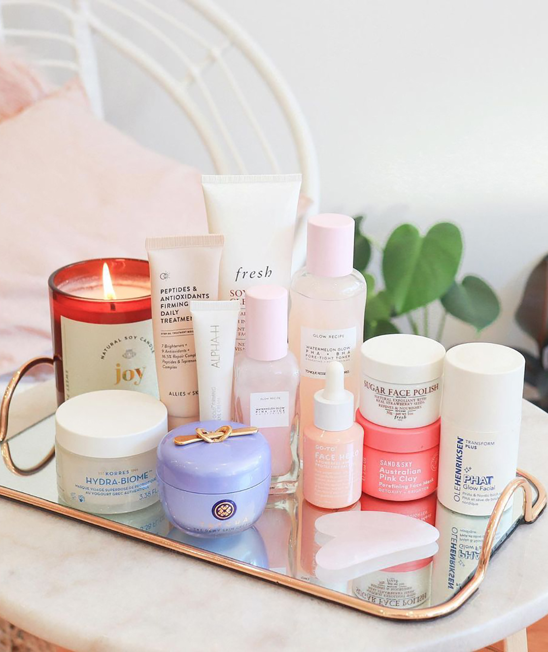 A photograph by one of Glow Candy's customers, shared to social media. The photo shows the 'Joy' candle positioned at the back of a tray of beauty prodcuts.