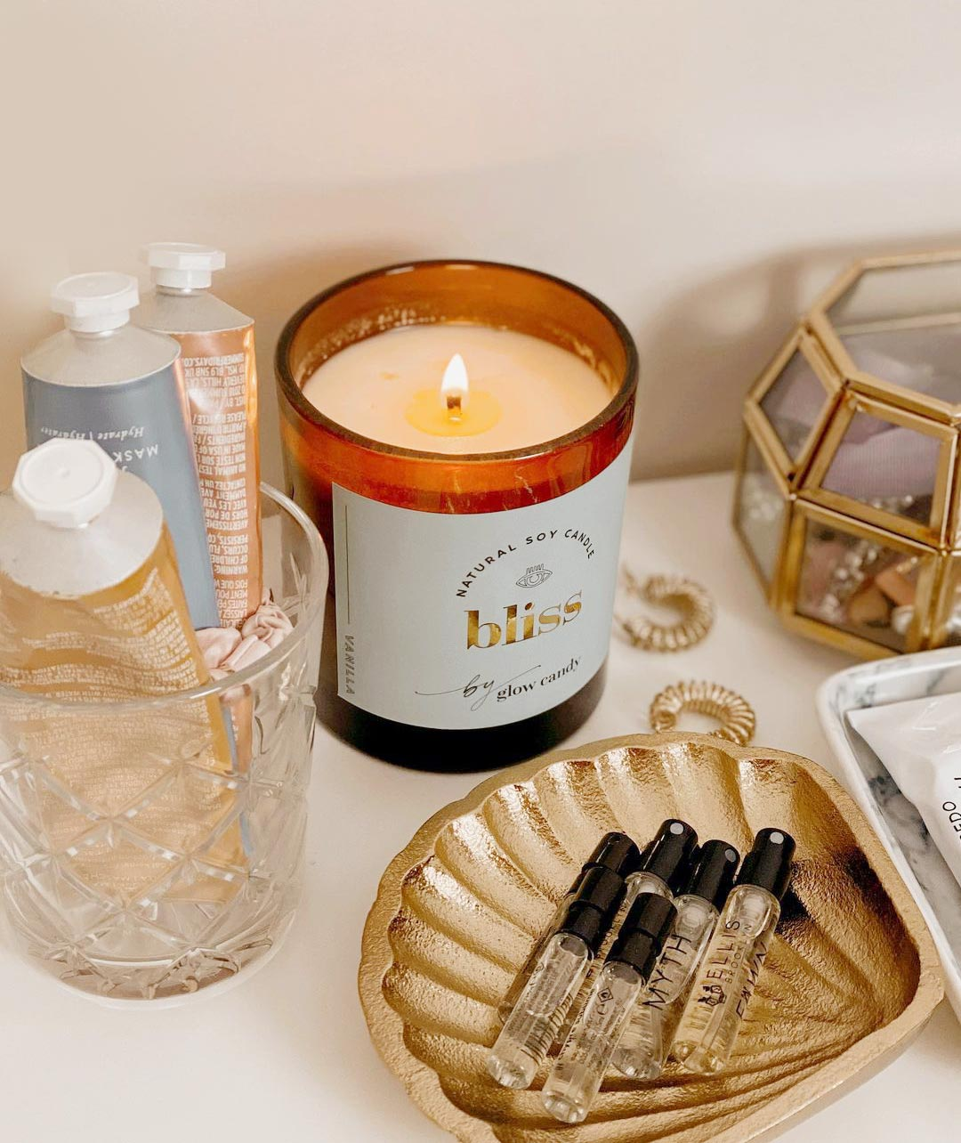 A photograph by one of Glow Candy's customers, shared to social media. The photo shows the 'Bliss' candle positioned on a counter alongside various beauty products.