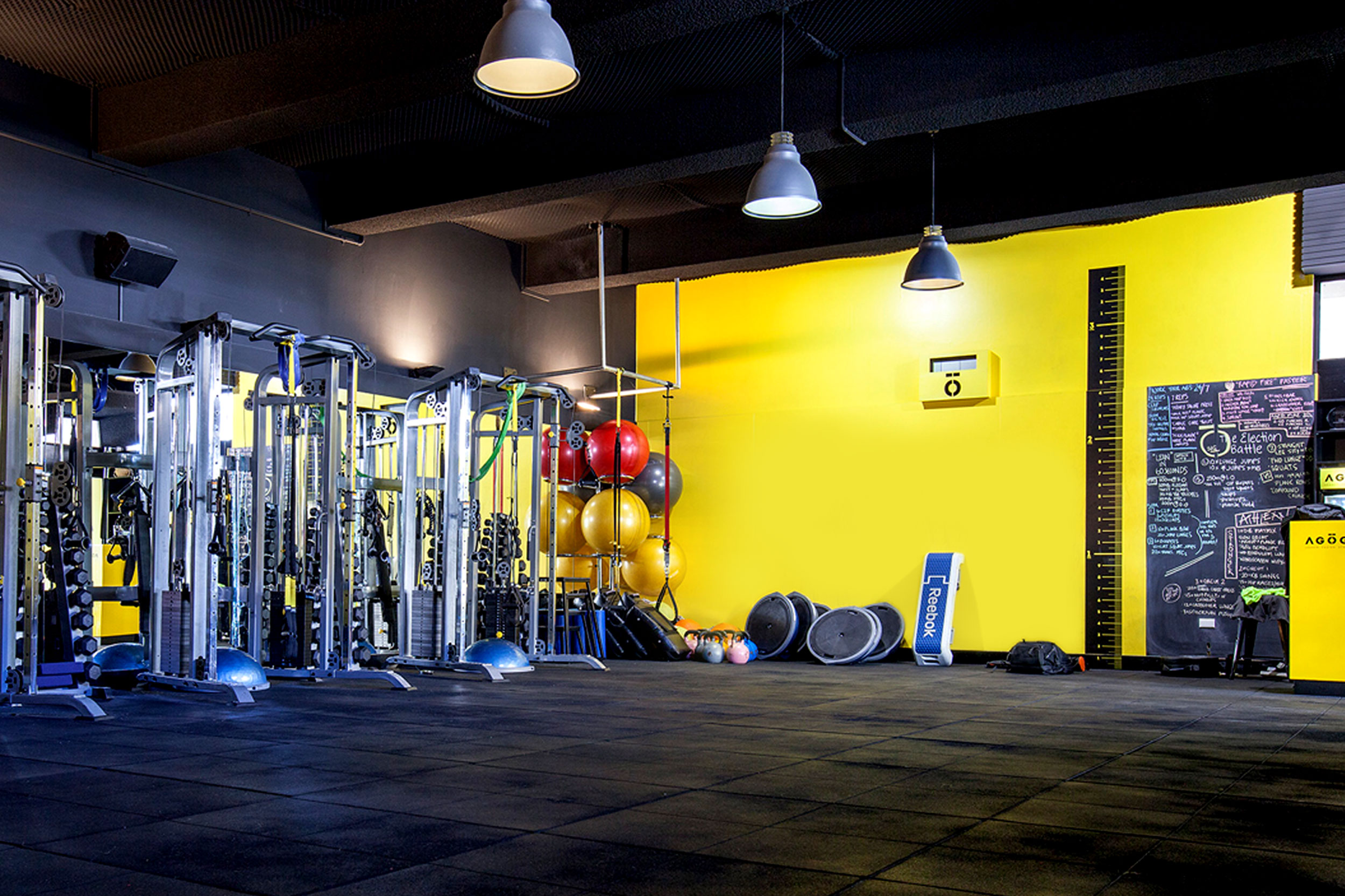 Agoga Bondi's gym area, featuring a branded clock on a bright yellow wall