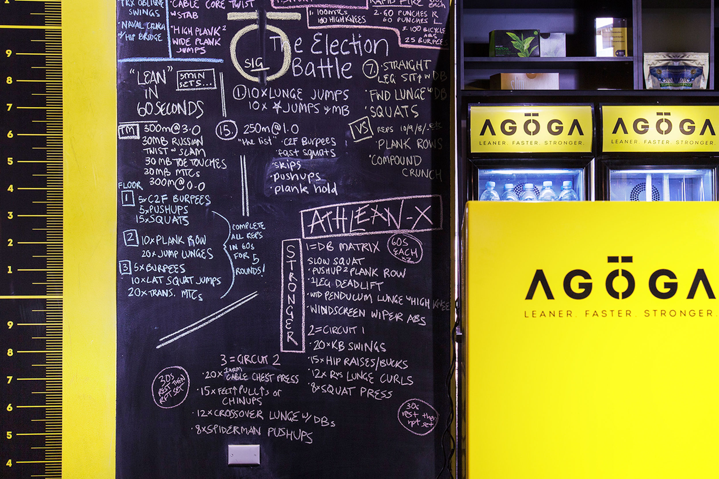 Agoga Bondi's reception area, featuring a branded front desk and branded fridges. To the left of the reception area is a black board covered in exercise instructions. The brand icon has been drawn in chalk by a staff member in the centre of the board.