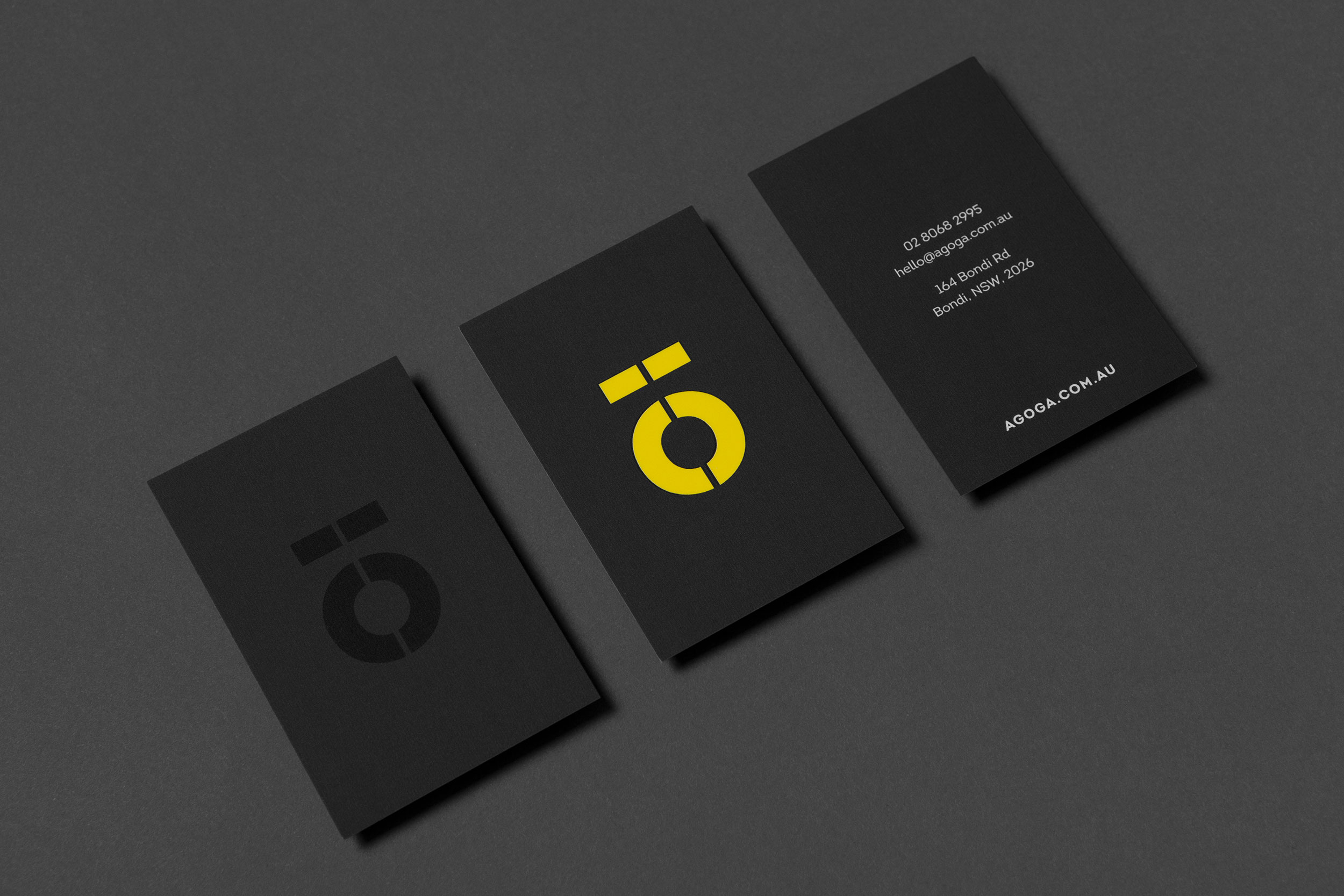 A close-up of a set of business cards designed for Agoga Bondi, featuring the brand icon and a very minimal back-panel design.