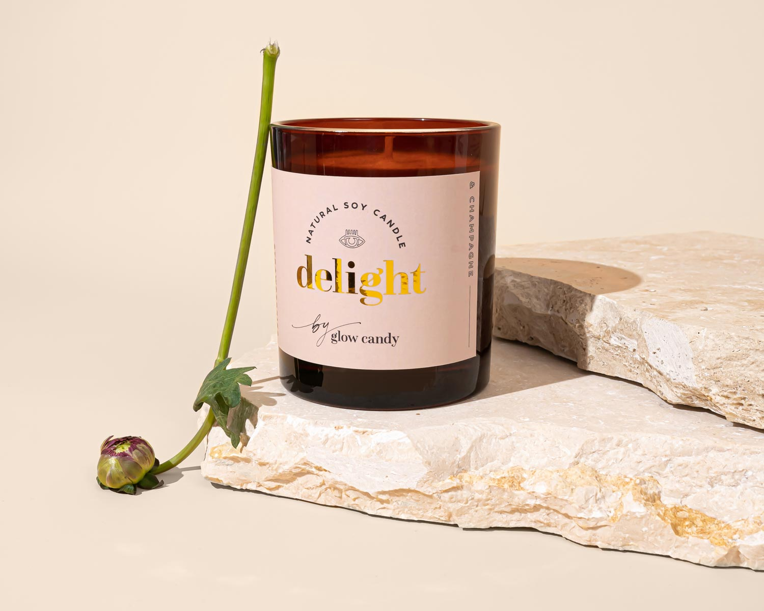Glow Candy's 'Delight' candle, photographed on a piece of natural stone with a flower bud by its side.