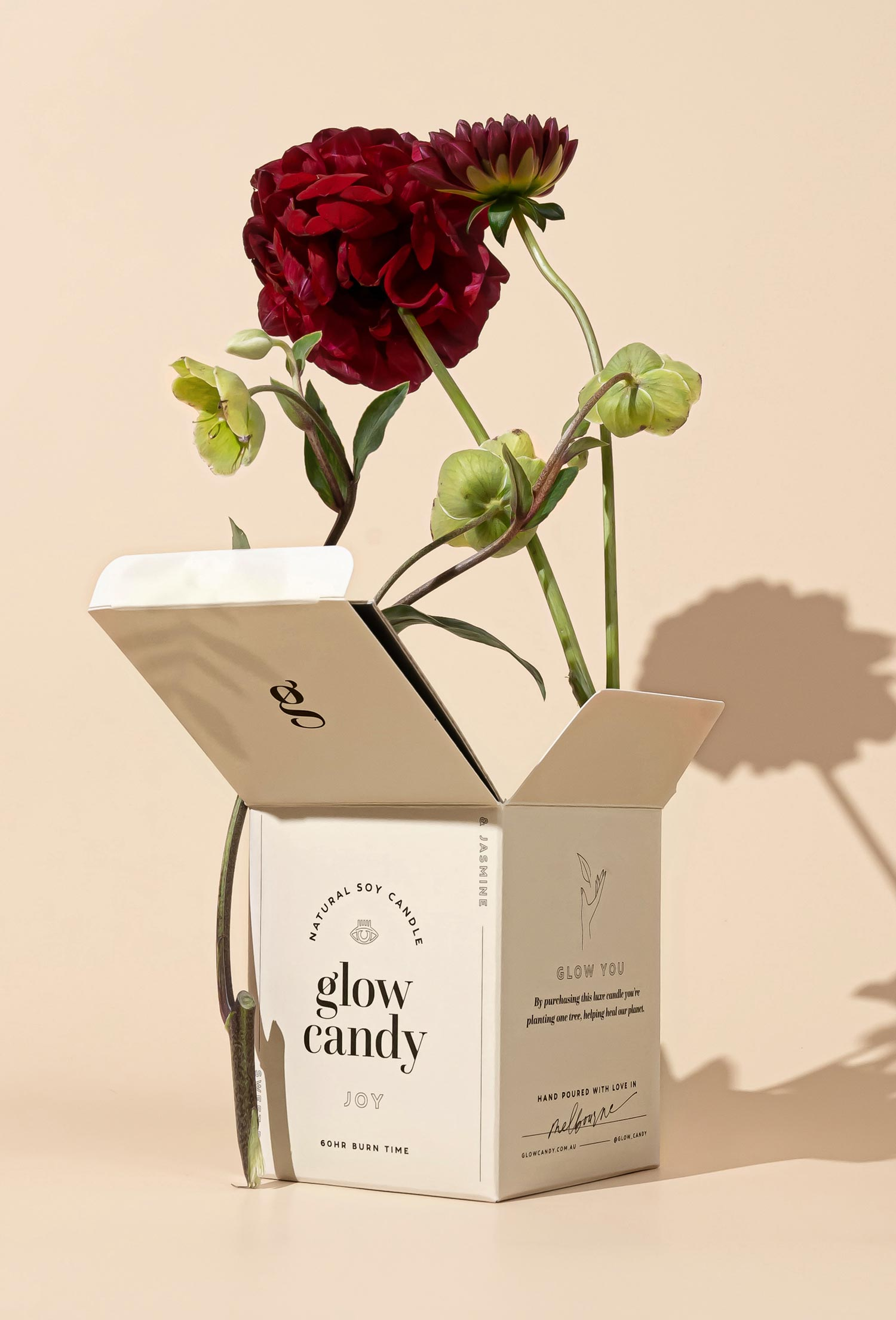 The outer box packaging for Glow Candy's 'Joy' scented candle, photographed in a studio with a rose in the box and a stark shadow behind it.