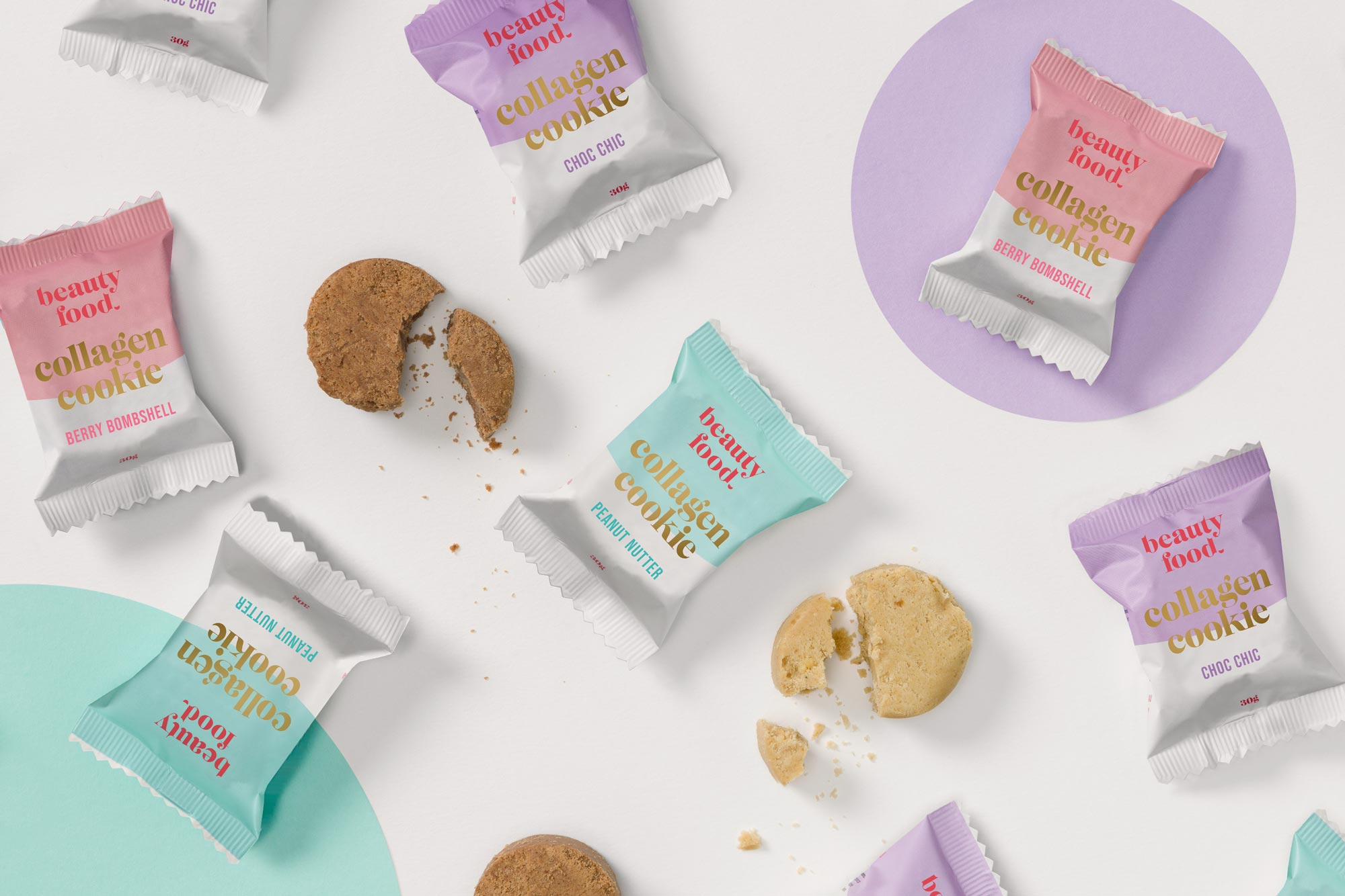 A flatly of multiple Beauty Food collagen cookies, including a mix of flavours. Some cookies have been opened and sit crumbled between the closed packets.