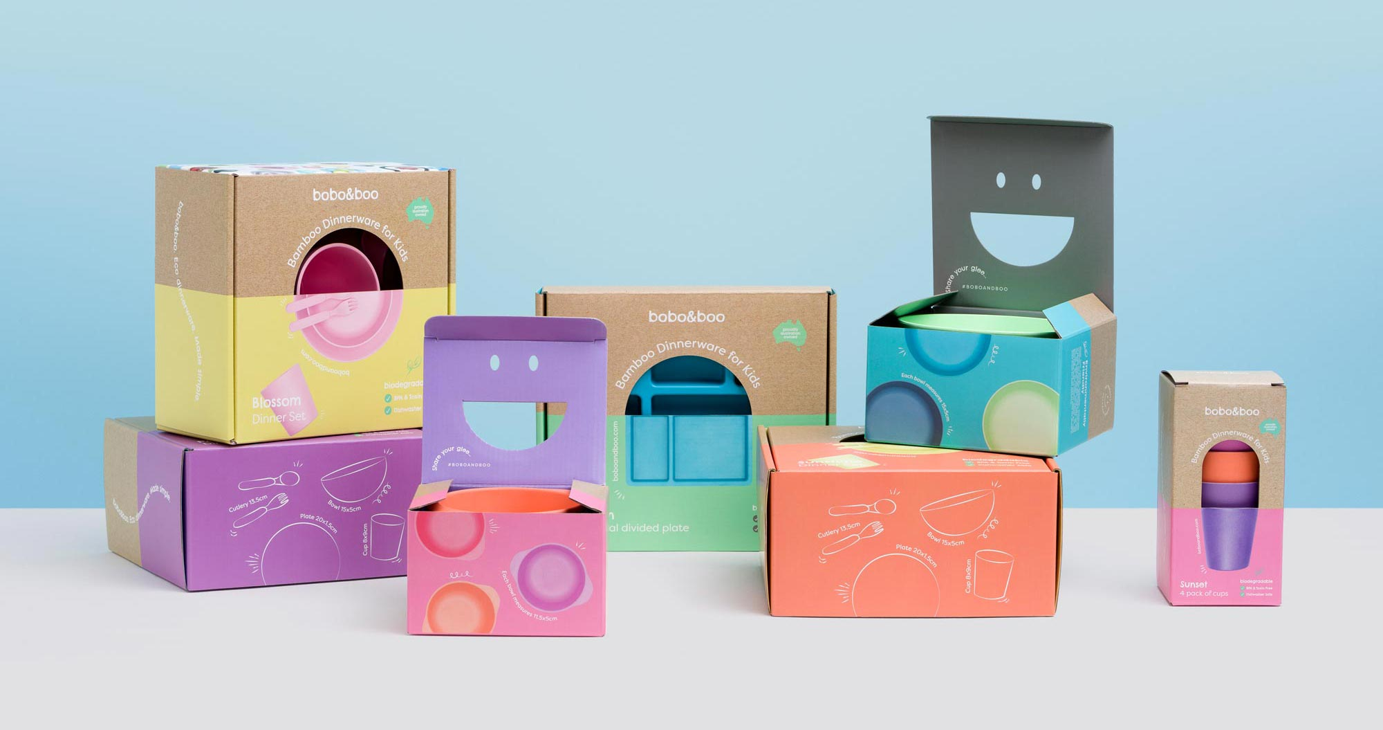 A large collection of product sets from Bobo & Boo's Bamboo range. Each set is in its own box, and two boxes have their lids open, showing the cut-out smile.