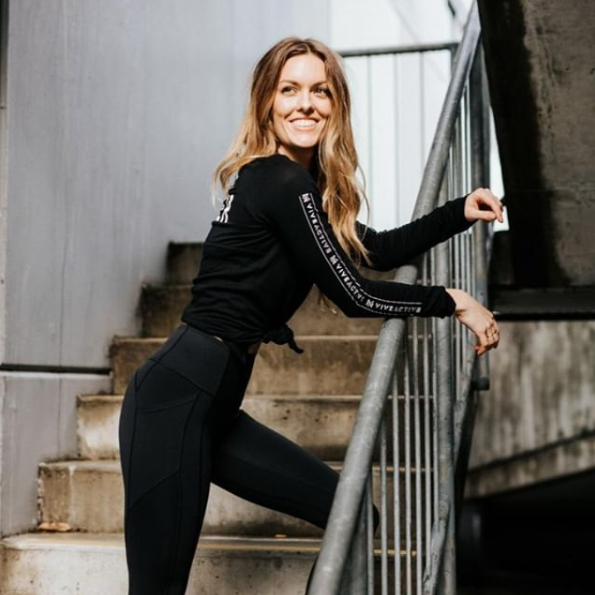 A Vive Active trainer poses while wearing branded merchandise
