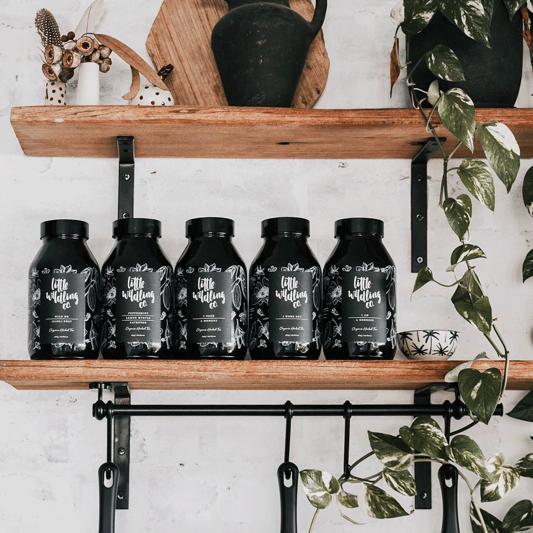 Five black glass jars of Little Wildling Co tea sit on the shelves at a trendy cafe. There are hanging vines falling over the shelf and a white brick wall behind them.