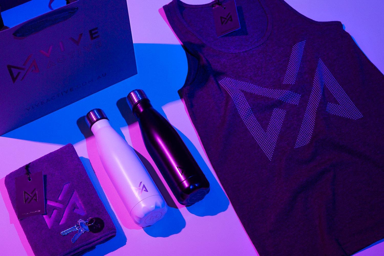 Merchandise Design for Vive Active, including drink bottles, a singlet, a sweat towel and a custom cardboard bag.