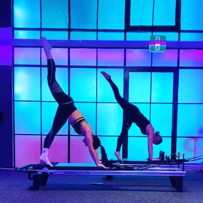 Two Vive Active Trainers perform a difficult pose, in sync, on a studio reformer. Behind them, a glass wall is completely illuminated with colour.