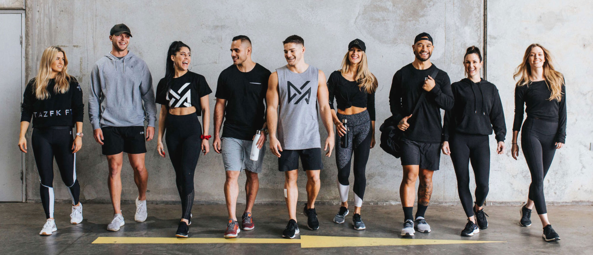 A large group of Vive Active trainers walk forward in a line, while wearing branded uniforms